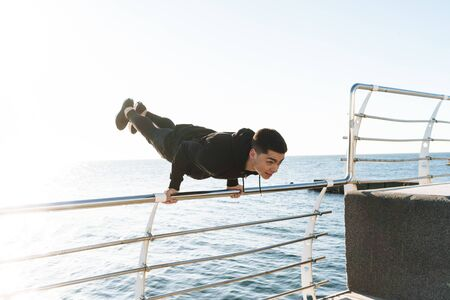 Photo of muscular guy 20s in black tracksuit doing acrobatics and jumping during morning workout by seaside Stock Photo