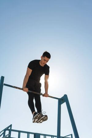 Photo of young sportsman 20s in black tracksuit doing acrobatics on horizontal gymnastic bar during morning workout by seaside