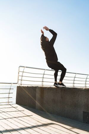 Photo of strong guy 20s in black tracksuit doing acrobatics and jumping during morning workout by seaside