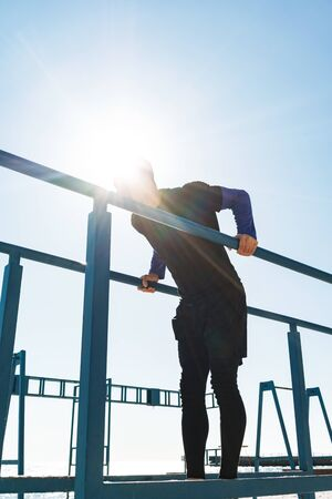 Photo of healthy guy 20s in black tracksuit doing acrobatics on horizontal gymnastic bar during morning workout by seaside Stock Photo
