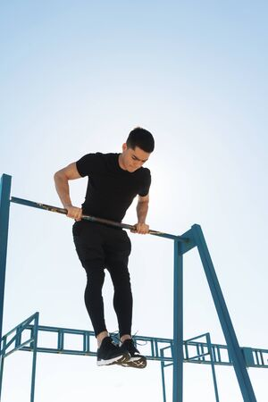 Photo of energetic guy 20s in black tracksuit doing acrobatics on horizontal gymnastic bar during morning workout by seaside