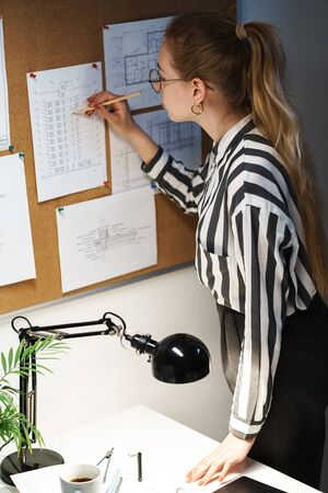 Confident pretty young businesswoman working at the office, using visualisation board