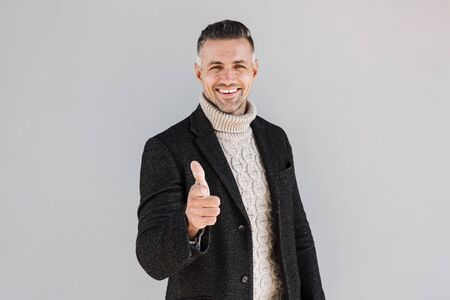 Attractive man wearing coat standing isolated over gray background, pointing finger at camera