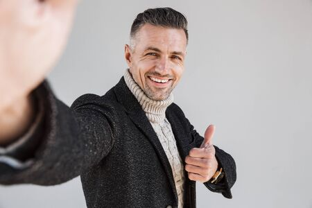 Attractive happy man wearing coat standing isolated over gray background, taking a selfie, giving thumbs up