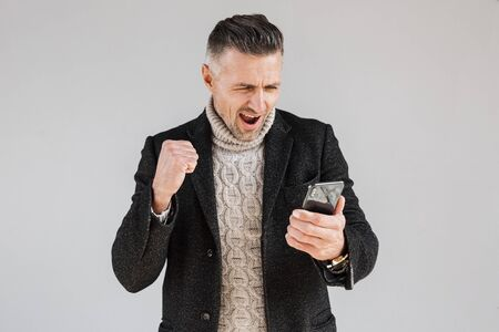 Attractive excited man wearing coat standing isolated over gray background, using mobile phone, celebrating