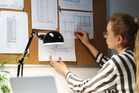 Photo of young blonde woman architect wearing glasses designing draft at workplace in office