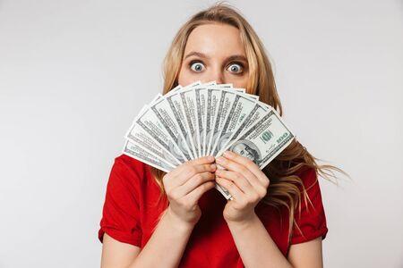 Bild der aufgeregten jungen hübschen schönen Frauenaufstellung lokalisiert über dem weißen Wandhintergrund, der Geld hält. Standard-Bild