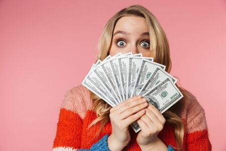 Image of young pretty beautiful woman posing isolated over pink wall background holding money covering face. Stock Photo - 126298641