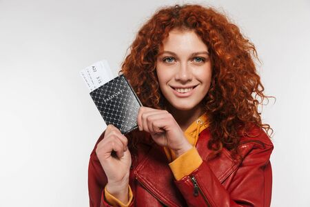 Portrait of positive redhead woman 20s wearing leather jacket holding passport and travel tickets isolated over white background