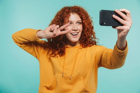 Portrait of an attractive redhead young woman standing isolated, taking a selfie, peace gesture 版權商用圖片