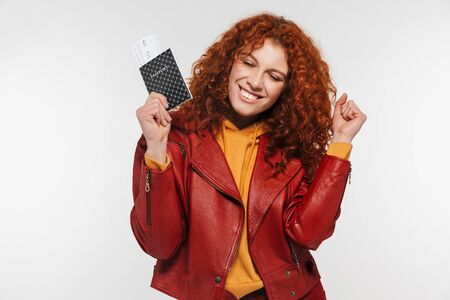 Portrait of alluring redhead woman 20s wearing leather jacket holding passport and travel tickets isolated over white background