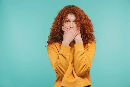 Photo of pretty woman 20s with curly ginger hair looking at camera and covering her mouth isolated over blue background