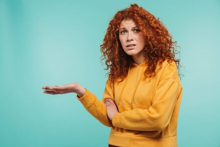 Photo of puzzled woman 20s with curly ginger hair holding copyspace on her palm isolated over blue background
