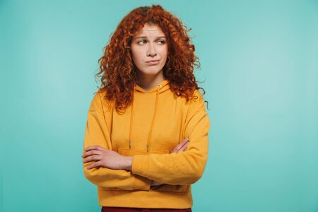 Photo of discontent woman 20s with curly ginger hair looking aside with arms crossed isolated over blue background