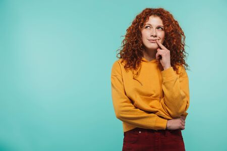 Portrait of an attractive pensive redhead young woman standing isolated Imagens