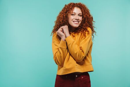 Photo of positive woman 20s with curly ginger hair smiling and looking at camera isolated over blue background