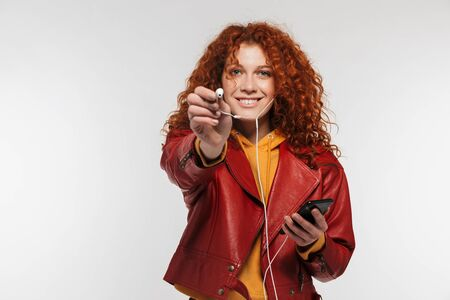 Portrait of pleased redhead woman 20s wearing leather jacket smiling and listening to music on smartphone isolated over white background