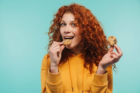 Portrait of joyous redhead woman 20s smiling and eating sweet cookies isolated over blue background