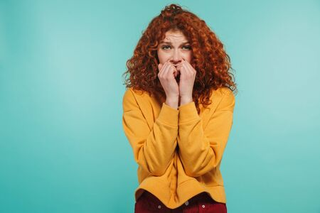 Photo of scared girl 20s with curly ginger hair looking at camera and biting her nails isolated over blue background 版權商用圖片