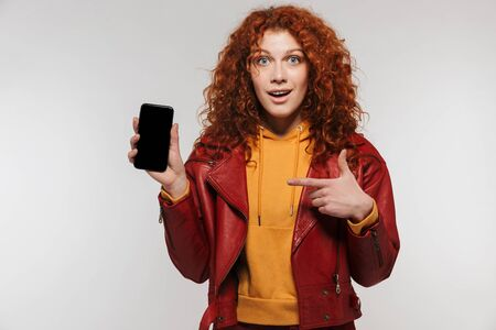 Portrait of cheery redhead woman 20s wearing leather jacket smiling and holding smartphone isolated over white background
