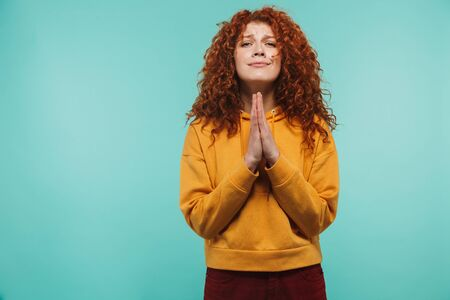 Image of attractive woman 20s with curly ginger hair keeping palms together and praying for good luck isolated over blue background