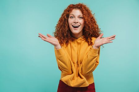 Photo of cheery girl 20s with curly ginger hair smiling and looking at camera isolated over blue background