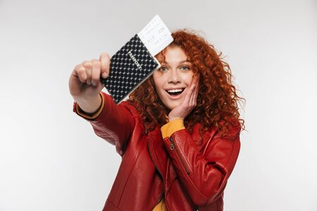 Portrait of elegant redhead woman 20s wearing leather jacket holding passport and travel tickets isolated over white background