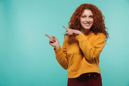 Image of caucasian woman 20s with curly ginger hair smiling and pointing finger at copyspace isolated over blue background