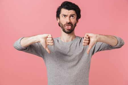 Portrait of an upset bearded man standing isolated over pink background, showing thumbs down Foto de archivo