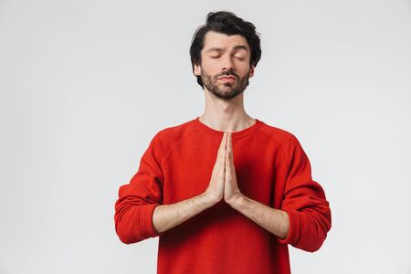 Picture of a handsome young concentrated man posing isolated over white wall background meditate. Stock Photo