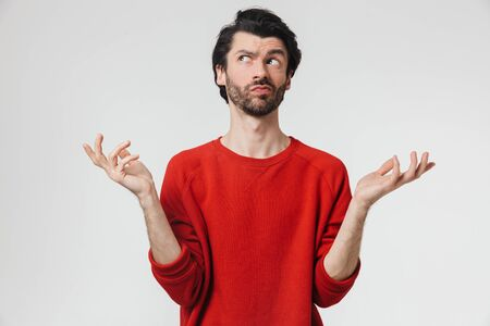 Handsome young confused bearded brunette man wearing sweater standing isolated over white background 스톡 콘텐츠