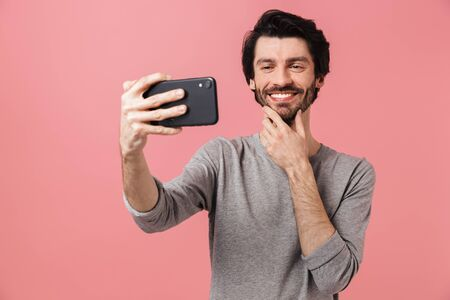 Handsome cheerful young bearded brunette man wearing sweater standing isolated over pink background, taking a selfie