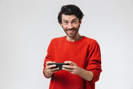 Handsome excited young bearded brunette man wearing sweater standing isolated over white background, playing games on mobile phone