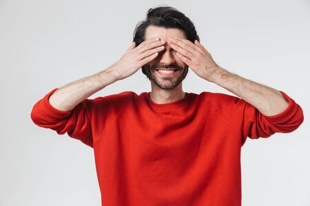 Image of a handsome young emotional man covering face with hands isolated over white wall background. Stock Photo