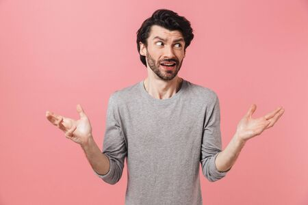 Young confused bearded brunette man wearing sweater standing isolated over pink background