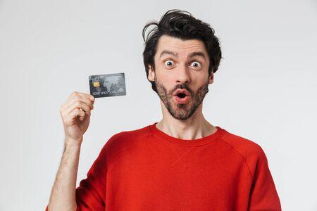 Bild eines hübschen jungen schockierten Mannes, der isoliert über weißem Wandhintergrund posiert, der Kreditkarte hält.