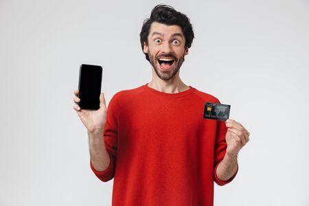 Handsome young bearded brunette man wearing sweater standing isolated over white background, showing blank screen mobile phone and credit card 版權商用圖片