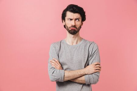 Handsome young confused bearded brunette man wearing sweater standing isolated over pink background 스톡 콘텐츠