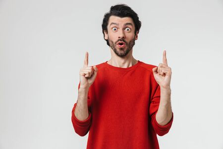 Handsome young bearded brunette man wearing sweater standing isolated over white background, pointing finger at copy space Stockfoto
