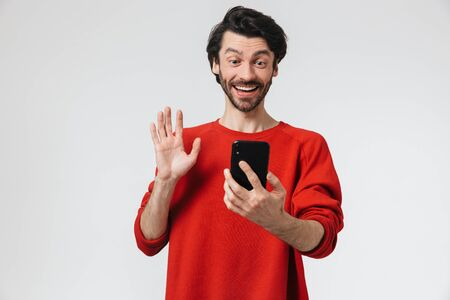 Handsome young bearded brunette man wearing sweater standing isolated over white background, having a video call