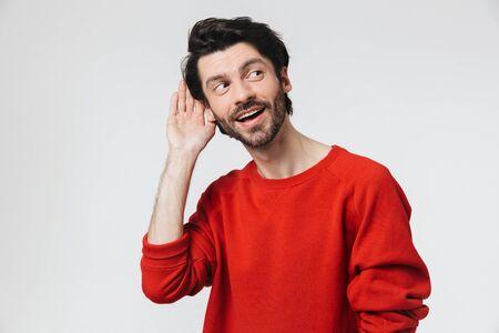 Hübscher junger bärtiger brünetter Mann, der einen Pullover trägt, der isoliert auf weißem Hintergrund steht und versucht, Geräusche zu hören?