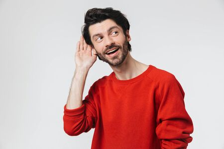 Handsome young bearded brunette man wearing sweater standing isolated over white background, trying to hear noise