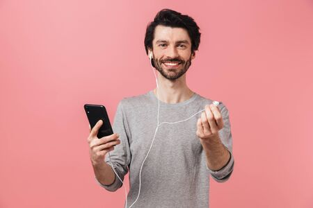 Handsome young bearded brunette man wearing sweater standing isolated over pink background, listening to music with earphones, holding mobile phone Banque d'images