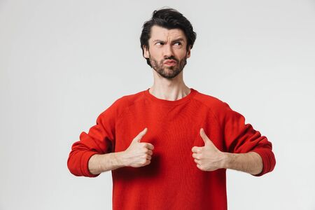 Handsome confused young bearded brunette man wearing sweater standing isolated over white background, showing thumbs up