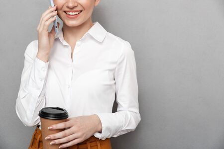 Portrait of pleased redhead businesswoman 20s in formal wear using smartphone in office and drinking takeaway coffee from plastic cup isolated over gray background