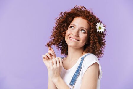 Image of a beautiful curly happy redhead girl posing isolated over purple background with flowers in hair.