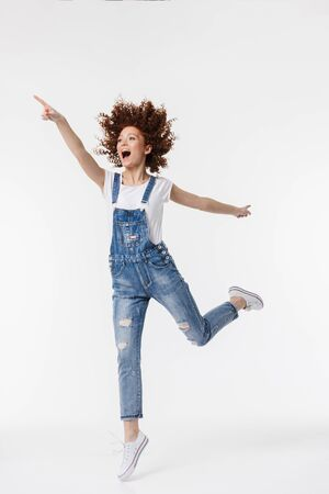 Full length of a cheerful young redhead curly haired girl wearing denim overalls posing isolated over white background