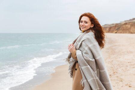 Hermosa joven pelirroja vistiendo abrigo, cubierto con una manta caminando en la playa Foto de archivo