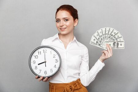 Image of cheerful redhead businesswoman 20s in formal wear holding big clock and bunch of money cash isolated over gray background Standard-Bild