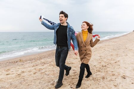 Cheerful young couple walking at the beach, carrying american flag